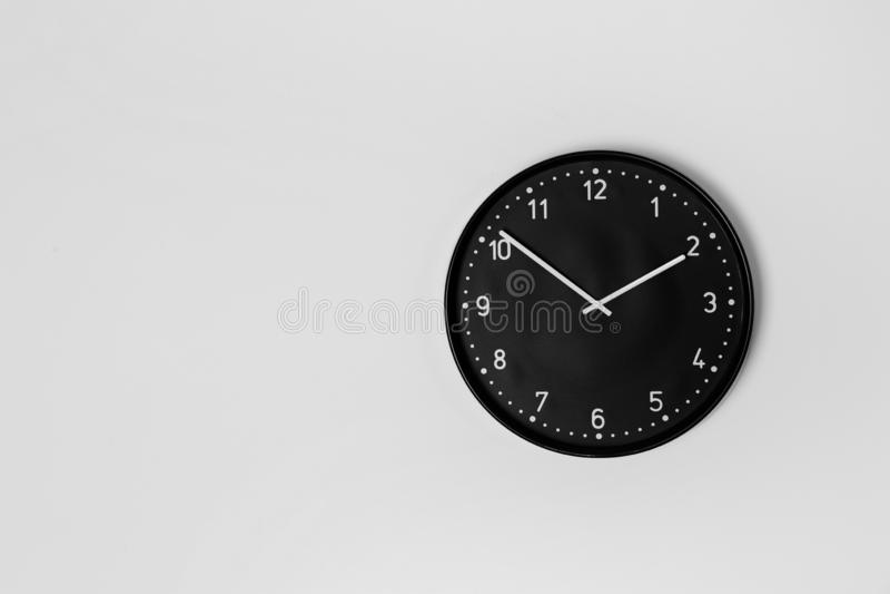 Стильные сетноые-аналогов часы вися на светлой стене стоковые фото