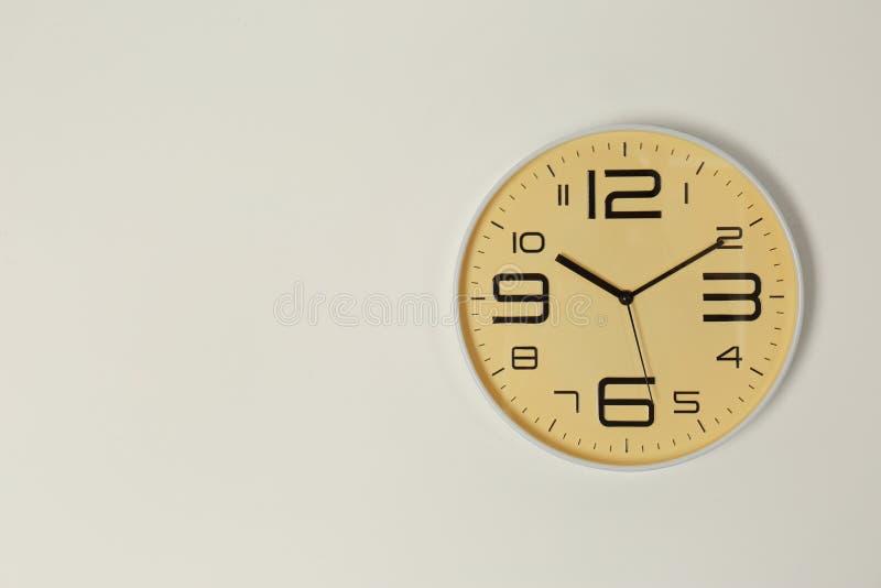 Стильные сетноые-аналогов часы вися на светлой стене стоковые изображения