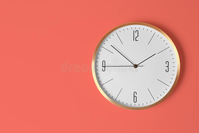 Стильные сетноые-аналогов часы вися на светлой стене стоковое фото rf