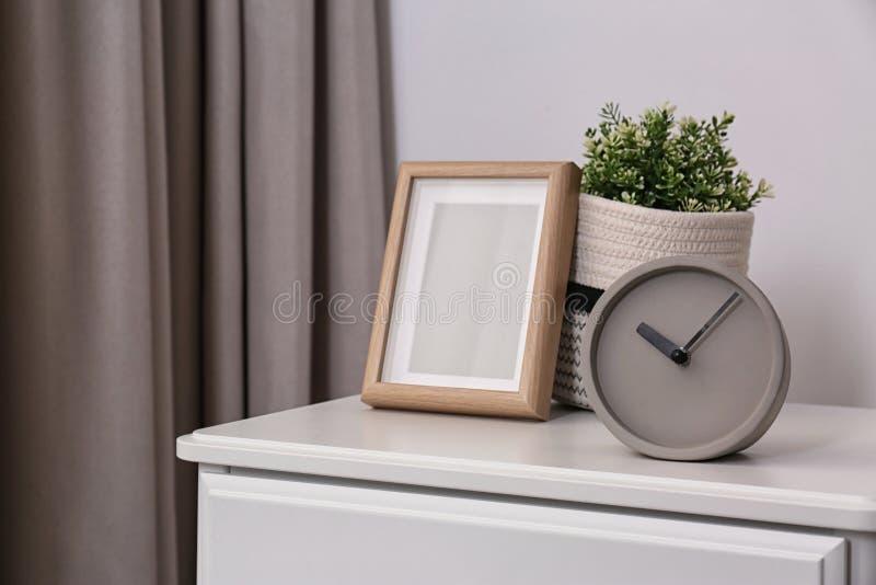 Стильные сетноые-аналогов часы, рамка фото и в горшке завод на комоде ящиков в комнате стоковое изображение