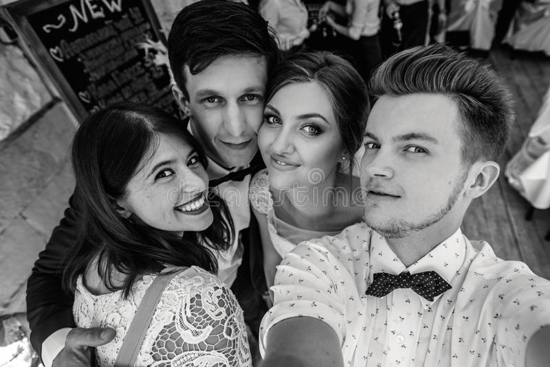 Стильные счастливые гости и жених и невеста имея смешные фото selfie группы на солнечный день стоковое изображение rf