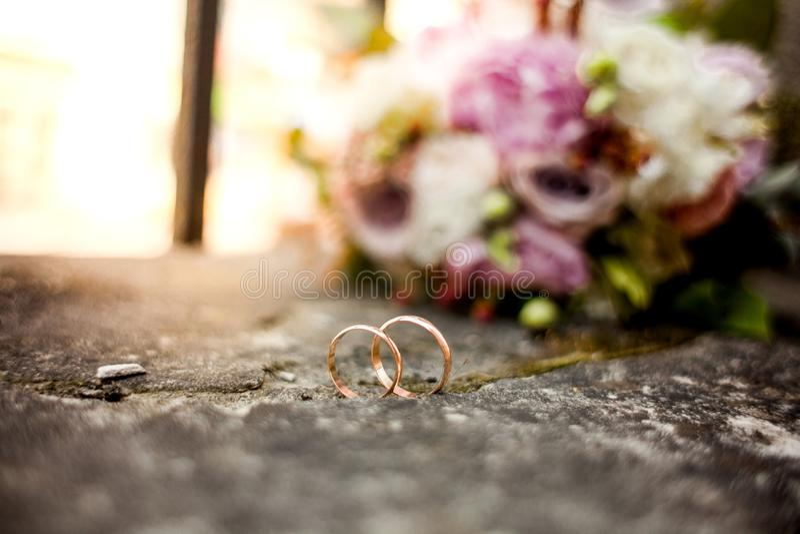 Стильный букет свадьбы цветет от роз куста, eustoma и обручальных колец золота на камне на природе предпосылки Свадьба cer стоковое фото