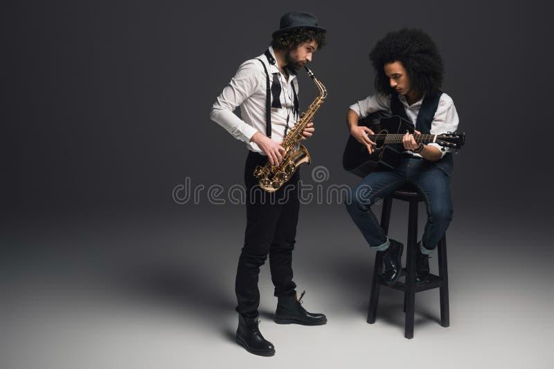 стильный дуэт музыкантов играя саксофон и акустическую гитару стоковое изображение rf