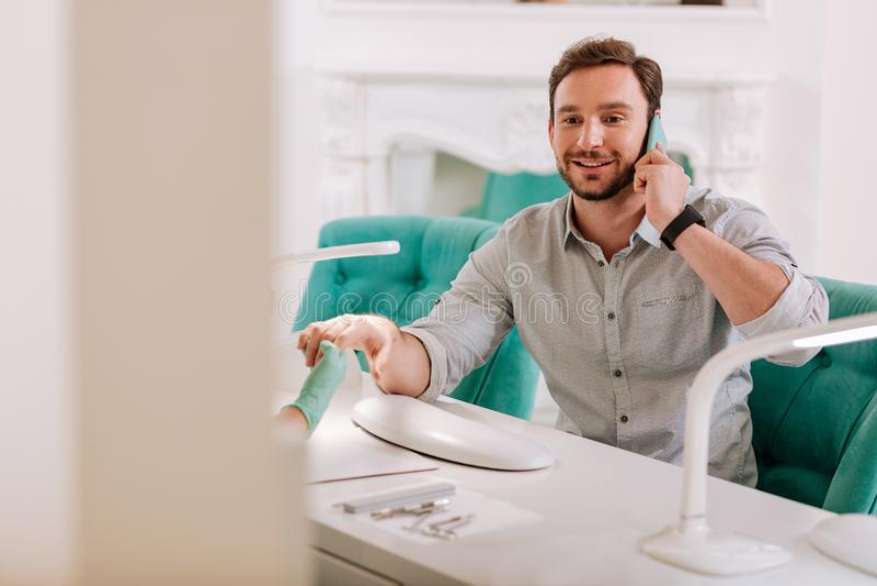 Стильный красивый человек сидя в салоне красоты получая маникюр стоковое фото