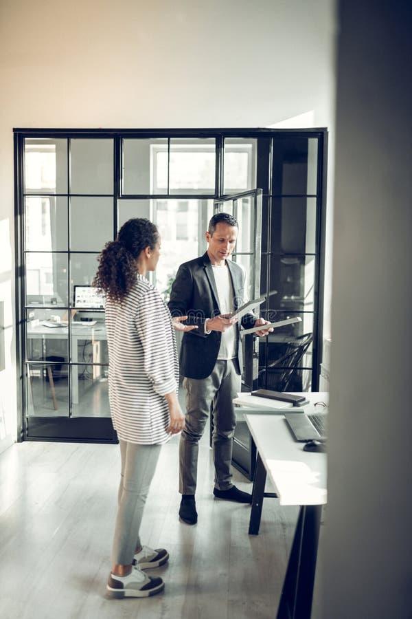 Стильный курчавый стажер приходя к ее серьезному боссу в офисе стоковые изображения