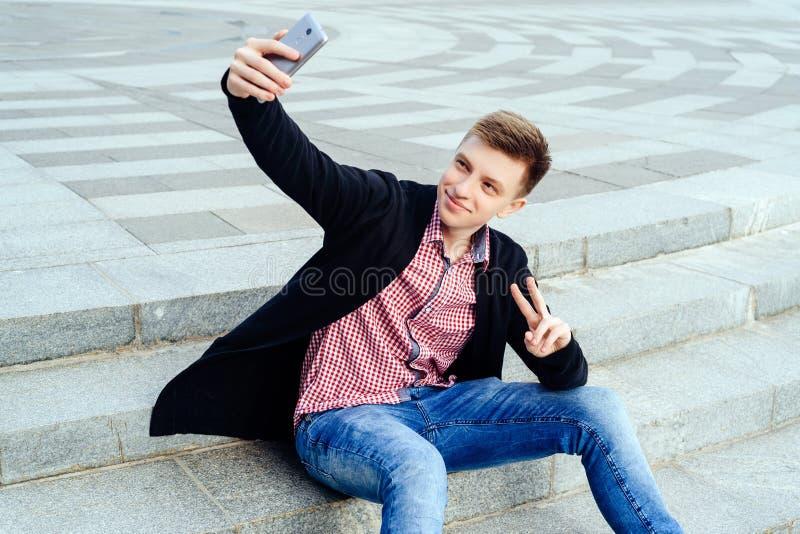 Стильный молодой усмехаясь человек в рубашке и джинсах шотландки стоковые изображения rf