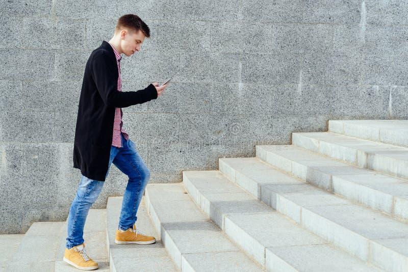 Стильный молодой человек в рубашке и джинсах шотландки идя вверх по лестницам стоковое изображение