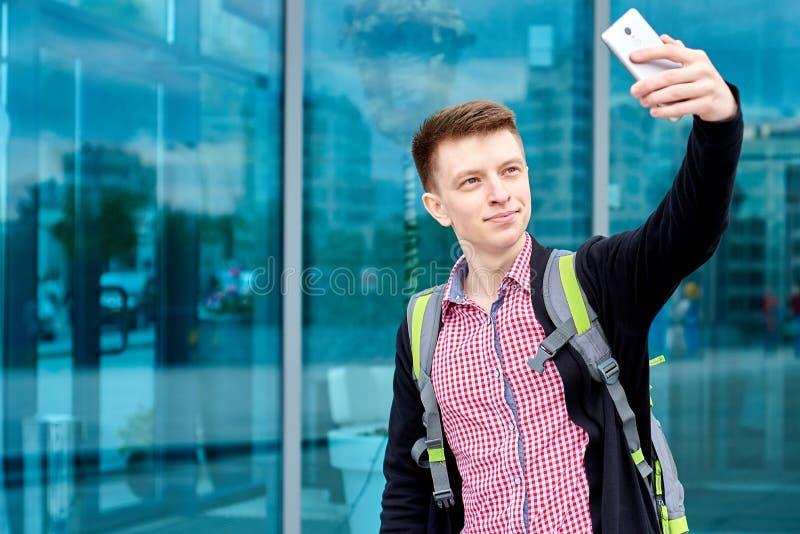 Стильный молодой человек в рубашке шотландки с положением рюкзака около стеклянного selfie здания и делать с камерой на мобильном стоковая фотография rf