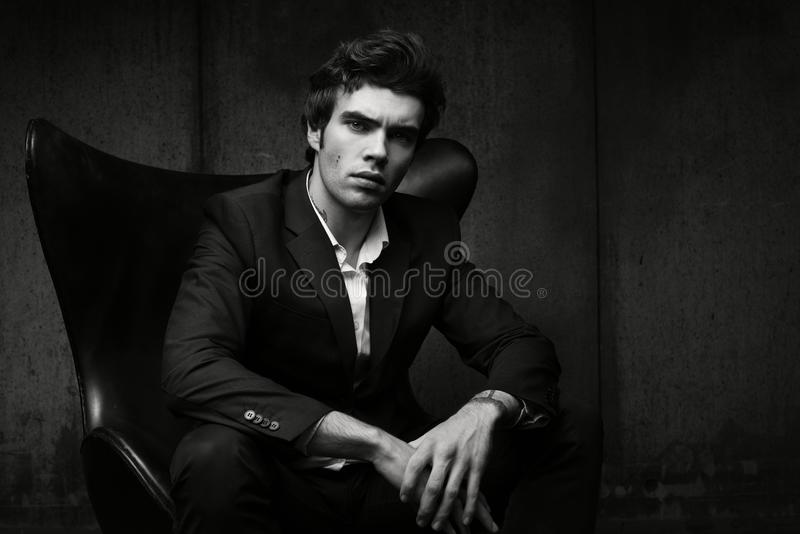 Стильный молодой человек сидя в стуле Черная куртка и белая рубашка стоковые фото