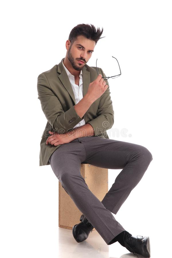 Стильный молодой человек сидя на деревянной коробке пока держащ стекла стоковое фото rf
