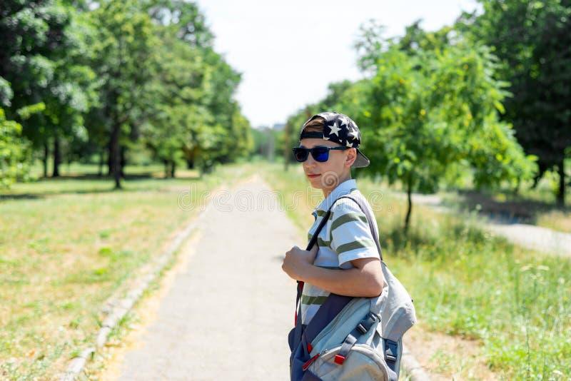 Стильный парень в крышке и солнечных очках и рюкзаке идет изучить стоковое фото rf