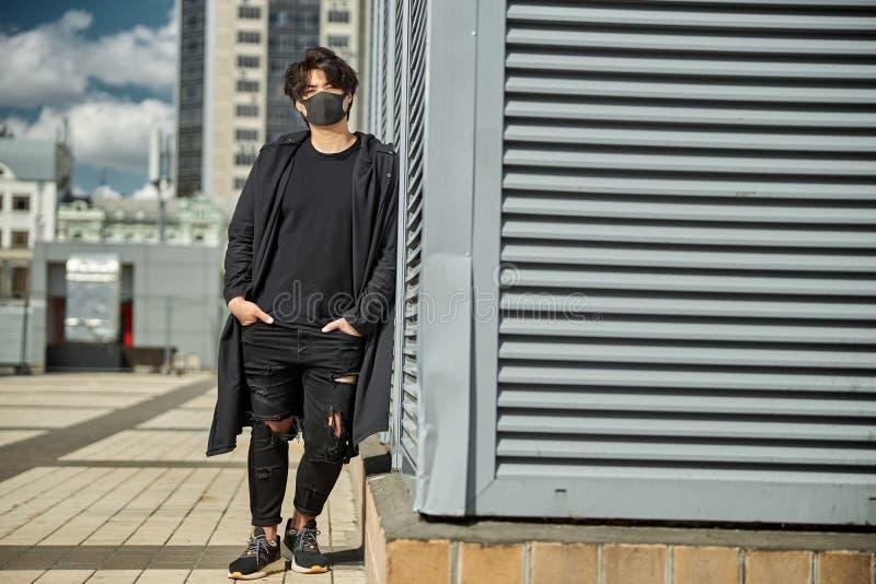 Стильный парень в медицинской маске лица, стоящий на улице стоковые изображения rf