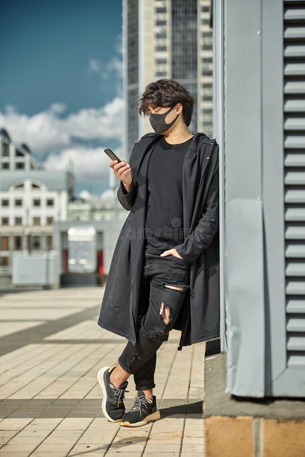 Стильный парень в медицинской маске лица с помощью мобильного телефона на улице стоковые фотографии rf