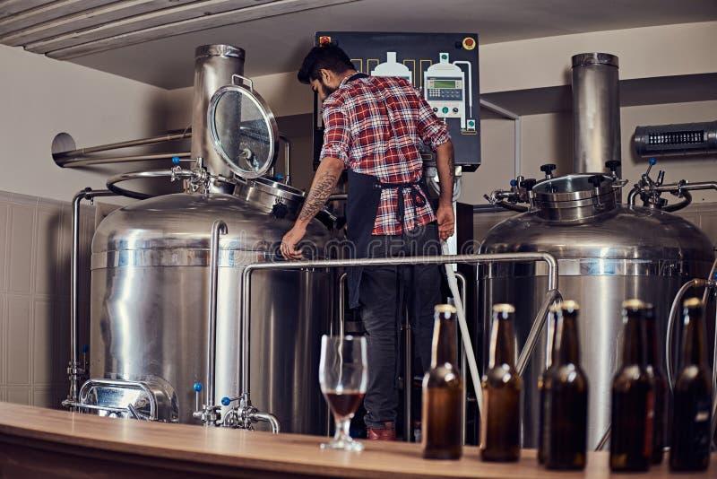 Стильный польностью бородатый индийский человек в рубашке и рисберме ватки контролирует процесс заваривать, стоя танк близко пива стоковое изображение rf