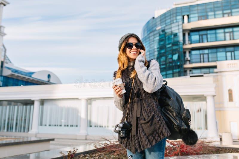 Стильный портрет города модной милой девушки, идя с coffe в современном центре города Европы Радостная молодая женщина внутри стоковые изображения rf