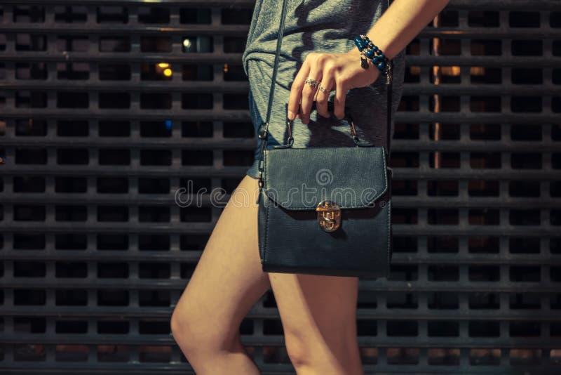 Стильный портрет моды ночи ультрамодной вскользь молодой женщины при черная кожаная сумка представляя около металлической городск стоковое изображение rf
