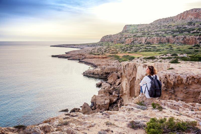 Стильный путешественник молодой женщины наблюдает красивый заход солнца на стоковые фото