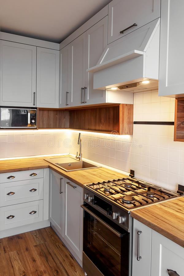 Стильный свет - серый интерьер кухни с современными шкафами с li стоковое изображение rf