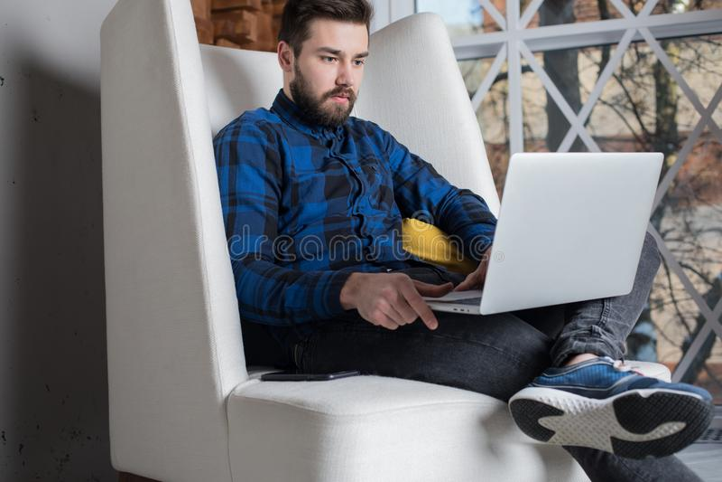 Стильный создатель человека распологает расстояние деятельности на портативном компьютере, усаживание в современном офисе стоковое фото rf