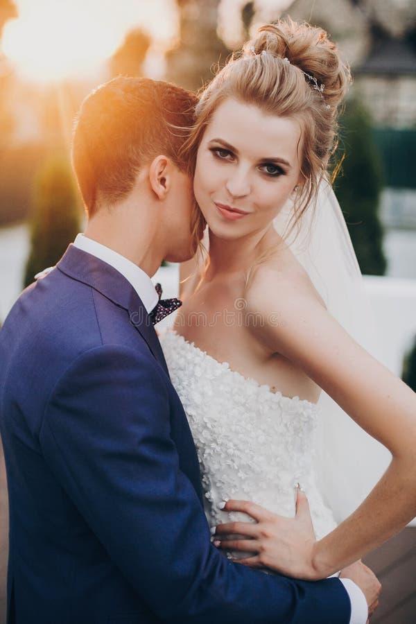 Стильный счастливый жених и невеста представляя в теплом свете захода солнца на приеме по случаю бракосочетания outdoors Шикарные стоковое изображение rf