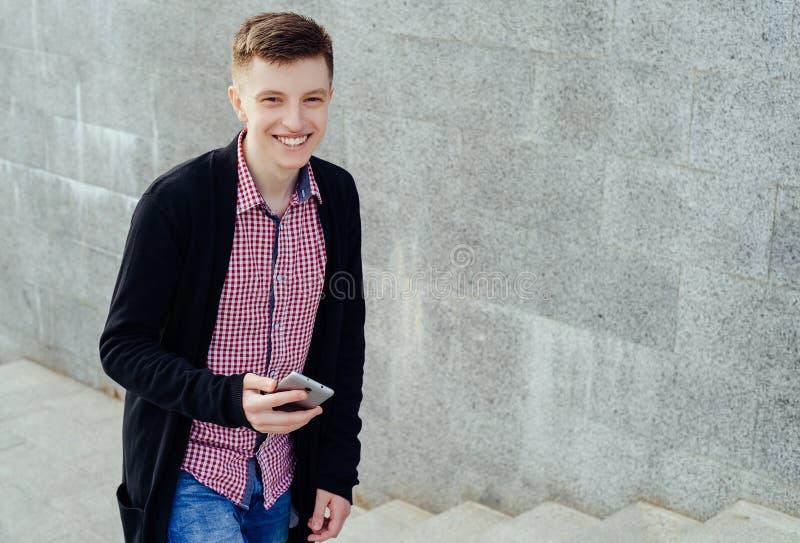 Стильный усмехаясь молодой человек в рубашке и джинсах шотландки стоковое фото