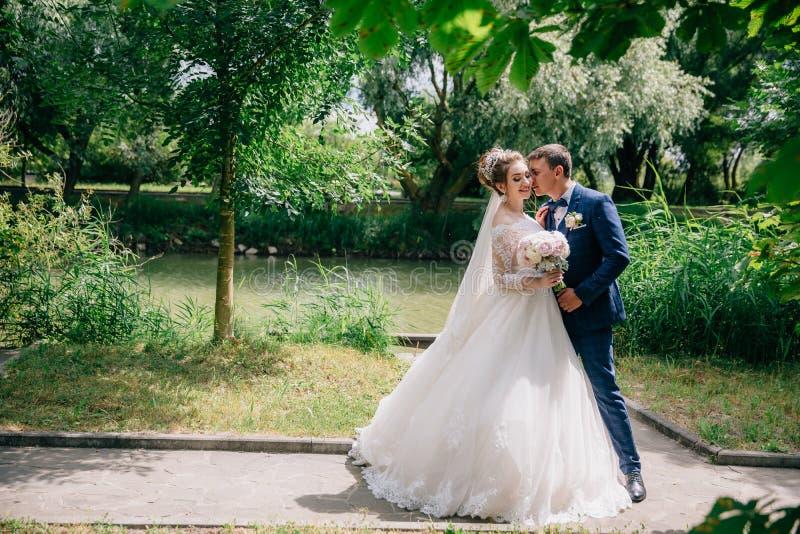 Стильный человек в костюме в клетке обнимает его любимое и хоронит его сторона в ее светлых волосах Невеста в шикарном платье стоковое изображение