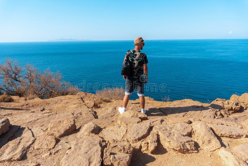 Стильный человек на скале морем стоковое фото rf