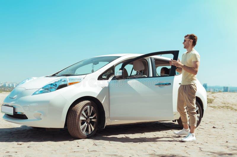 Стильный человек нося бежевые брюки стоя около его нового причудливого автомобиля стоковые фото