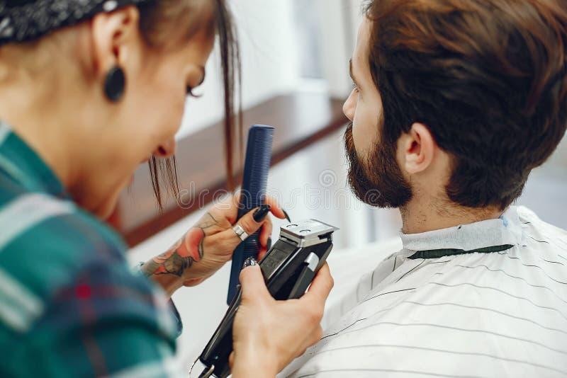 Стильный человек сидя в парикмахерскае стоковое фото rf