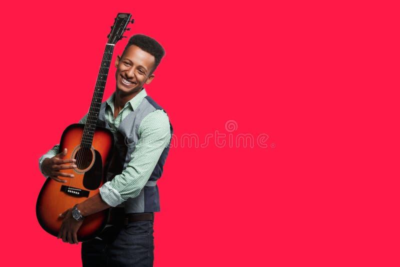 Стильный человек с гитарой в студии Молодой усмехаясь человек хипстера представляя с гитарой в его оружиях на красной предпосылке стоковое изображение rf