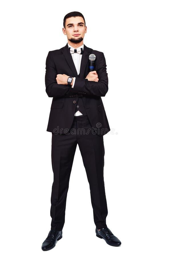 Стильный элегантный человек в черном костюме с микрофоном в его руке стоковое фото rf