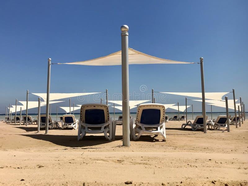 Стильный lounger в желтом песке, который нужно греть на солнце sunbed на пляже летом под открытым небом стоковые фотографии rf
