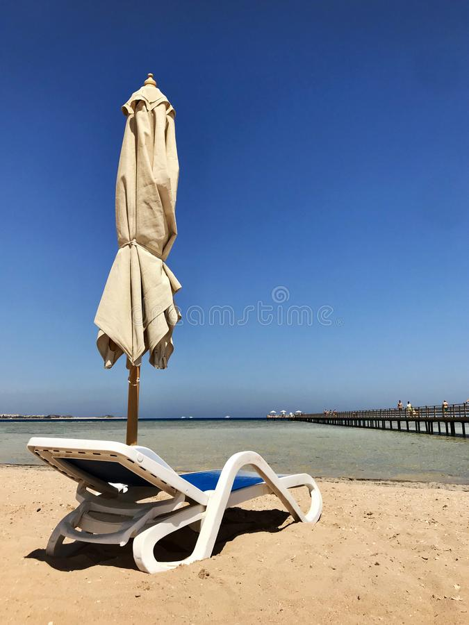 Стильный lounger в желтом песке, который нужно греть на солнце sunbed на пляже летом под открытым небом стоковое фото rf