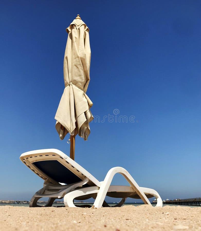Стильный lounger в желтом песке, который нужно греть на солнце sunbed на пляже летом под открытым небом стоковая фотография rf