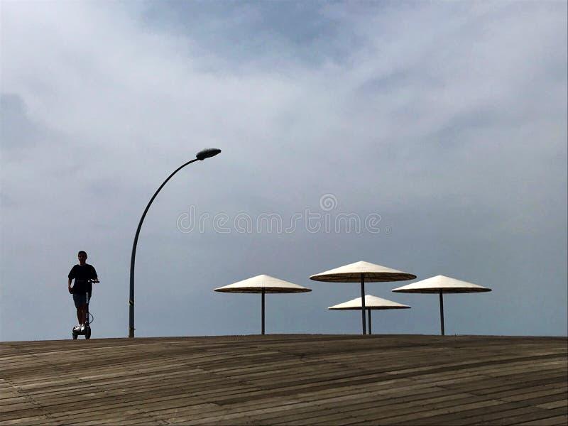 Стильный lounger в желтом песке, который нужно греть на солнце sunbed на пляже стоковое фото