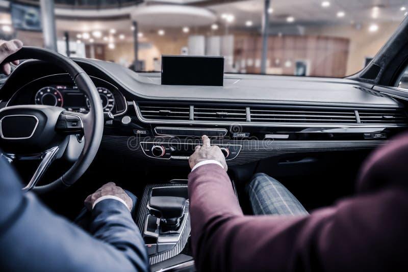 2 стильных бизнесмена сидя в роскошном автомобиле с кожаным интерьером стоковое фото