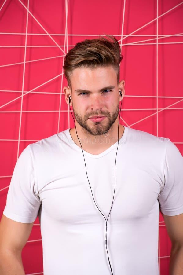 Стиль причёсок человека небритый бородатый стильный слушает музыка или наушники речи мотировать Слушает радио музыки с портативно стоковые фото