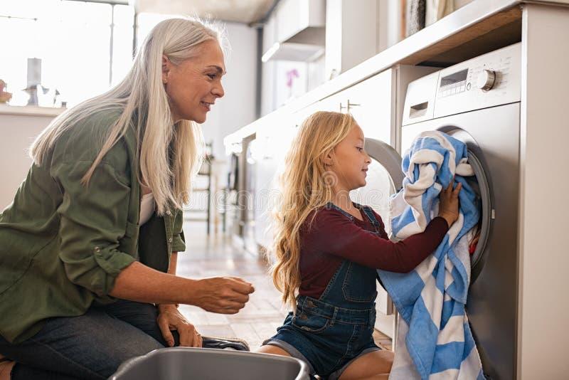 Стиральная машина маленькой девочки нагружая стоковые фотографии rf