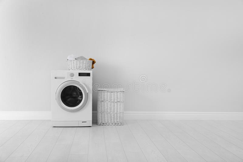 Стиральная машина с прачечной и корзина около стены стоковые фотографии rf