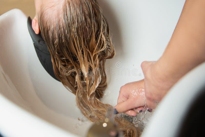 Стирка светлых волос с шампунем в роскошном салоне красоты стоковая фотография rf