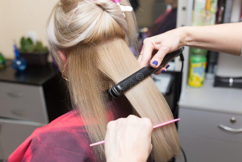 Стилизатор кладет волосы ` s женщин на плиту стоковое изображение rf