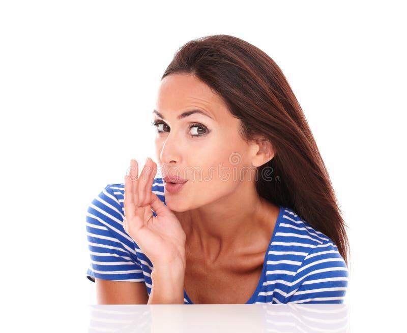 Стильная дама в голубой футболке шепча секрету стоковые изображения