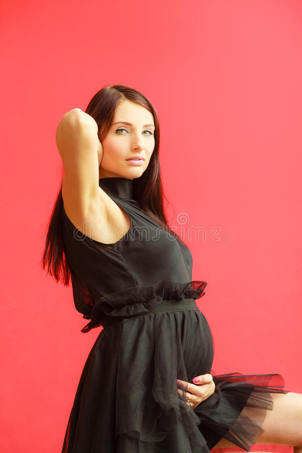 Стильная беременная женщина в черноте стоковые фотографии rf