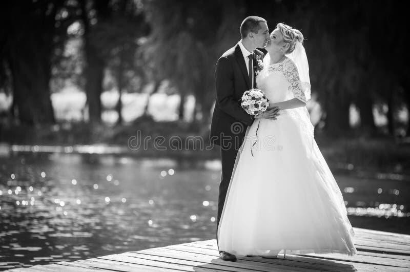 Стильная белокурая кавказская счастливая невеста с groom представляет на th стоковое изображение