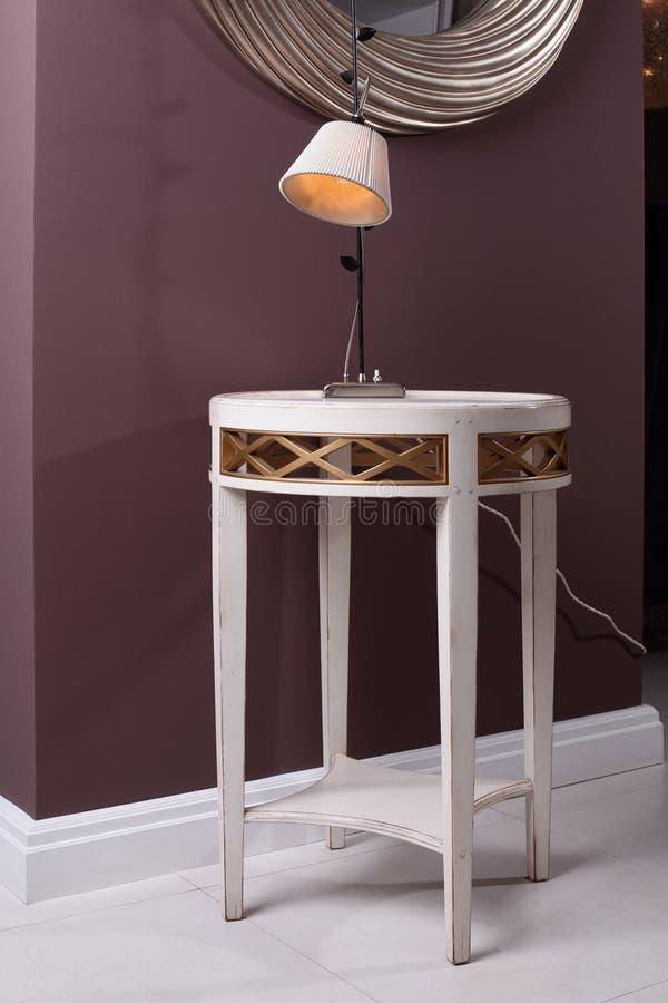Стильная и совершенно новая таблица с лампой и зеркалом стоковое изображение rf