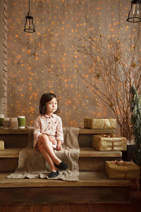 Стильная маленькая девочка в свете - розовое платье сидит в рождестве de стоковые изображения rf