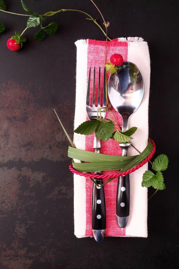 Стильная сервировка стола с красными шнуром и листьями стоковое изображение