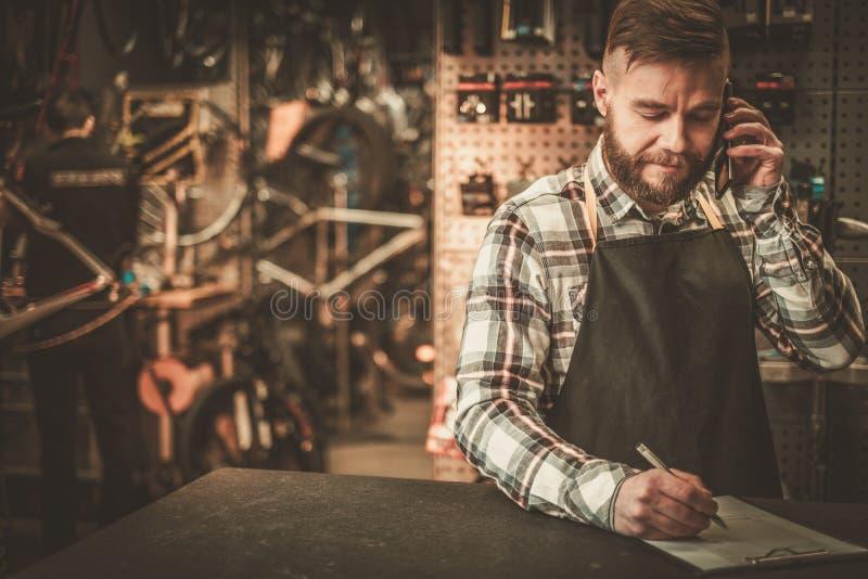 Стильный механик велосипеда принимает заказ телефоном в его мастерской стоковое изображение rf