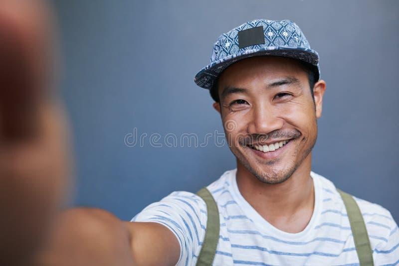 Стильный молодой азиатский человек принимая selfie снаружи стоковое изображение