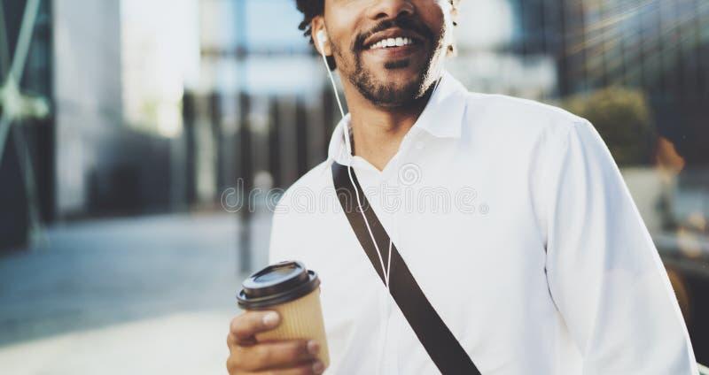 Стильный молодой американский африканский человек в наушниках идя на солнечный город с кофе взятия прочь и наслаждаясь для того ч стоковое изображение